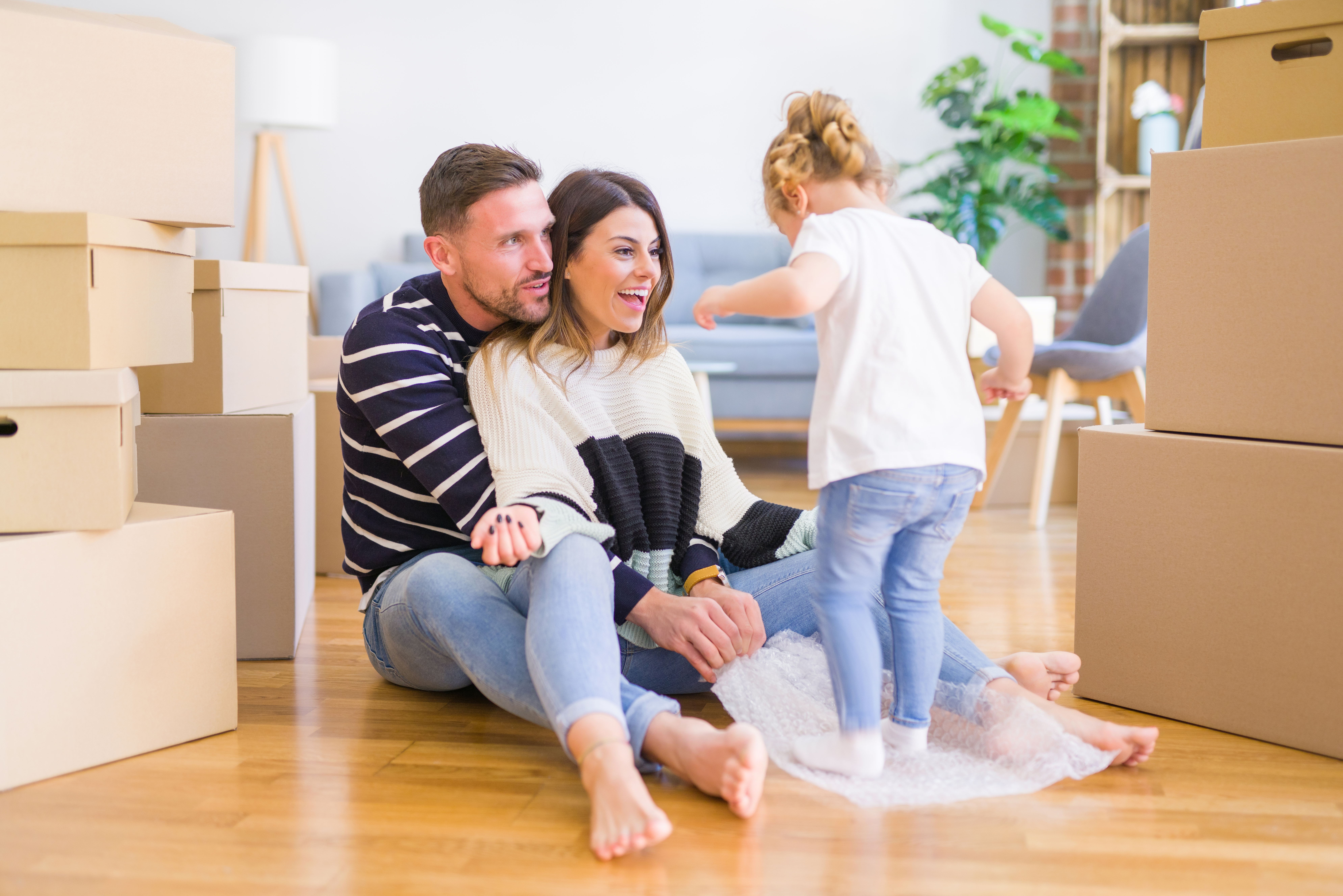 man, woman, and child with moving boxes