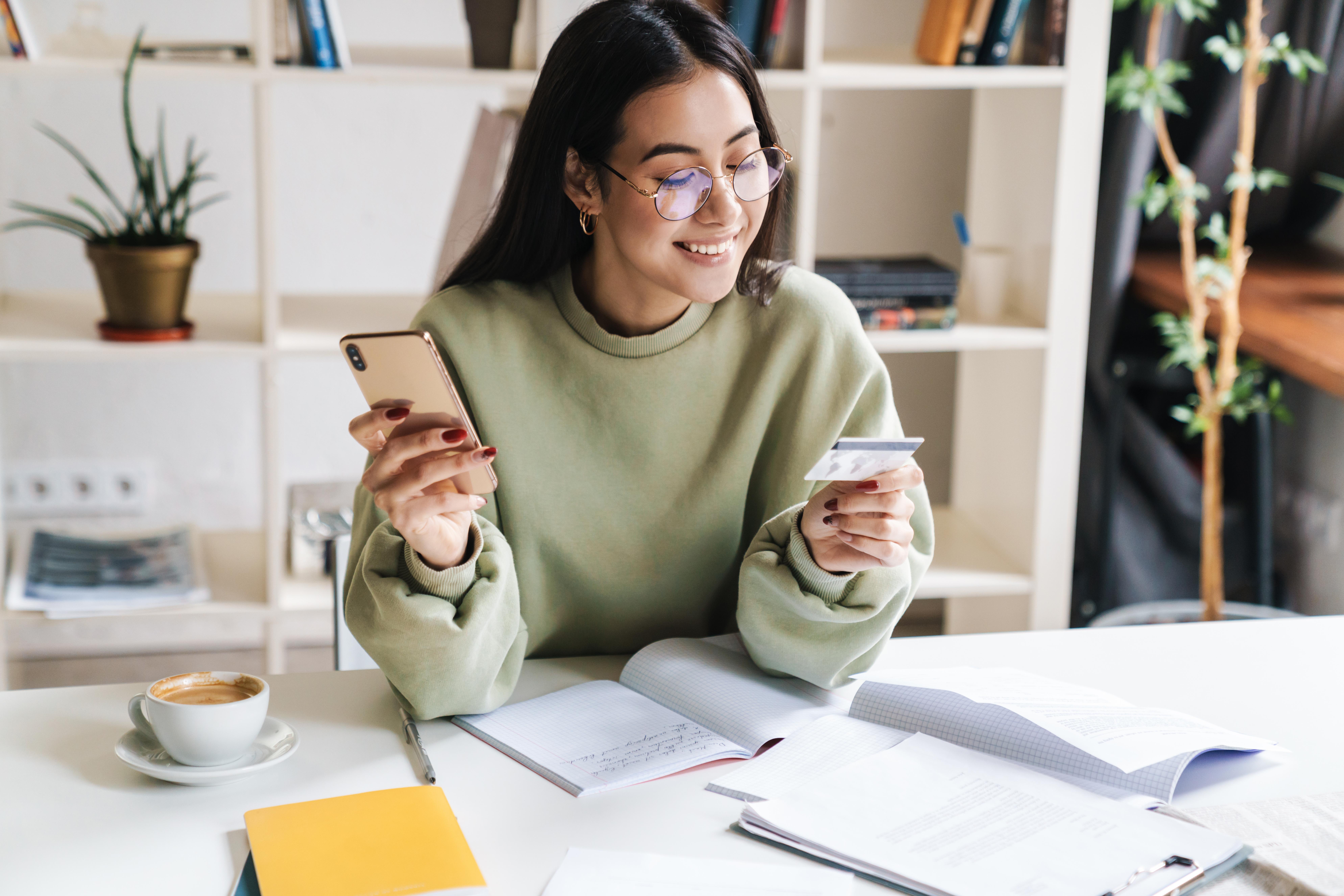 girl using phone and debit card