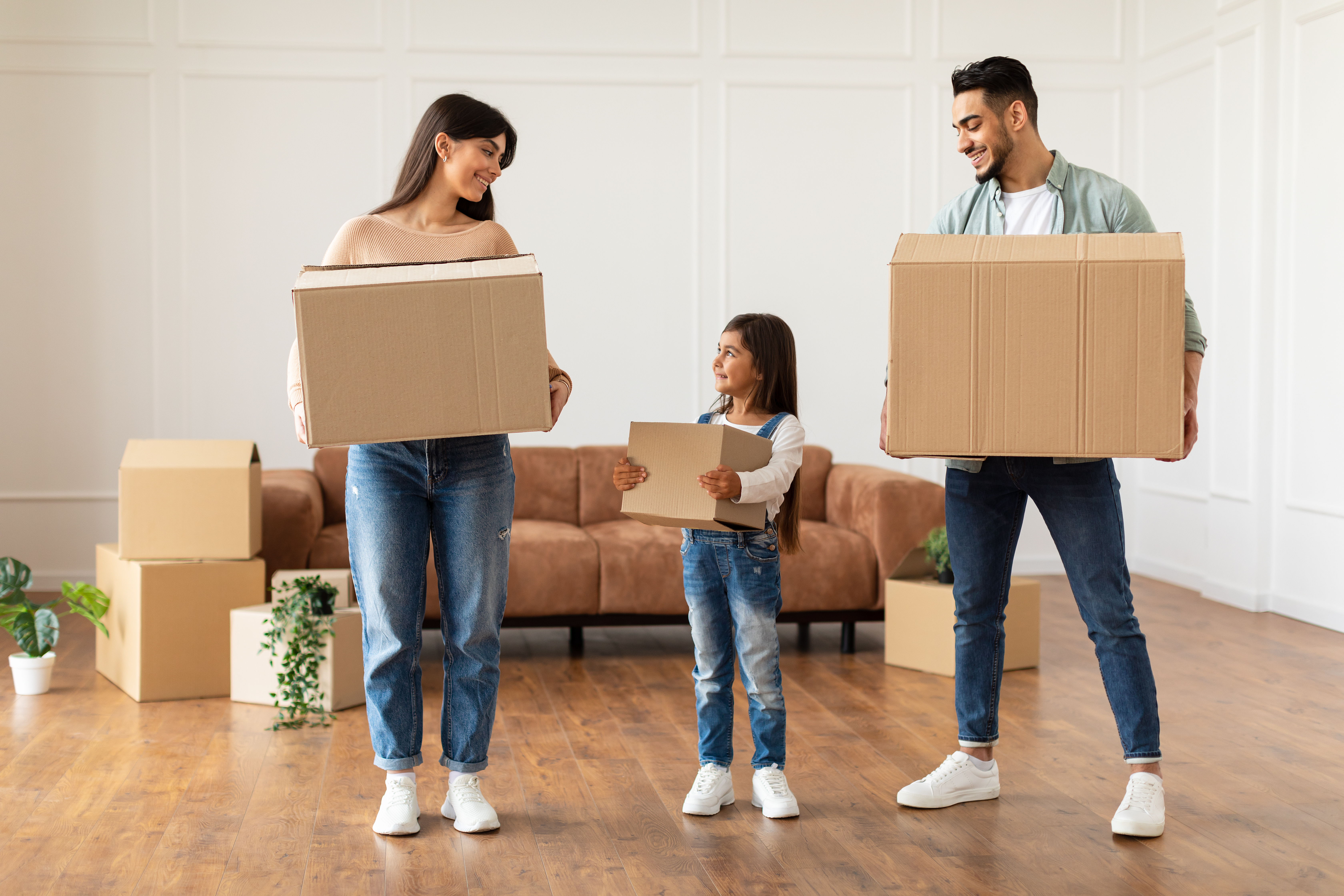 Parents and child holding moving boxes
